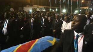 Jean-Marc Kabund, vice-président de l'Assemblée nationale et Monseigneur Gérard Mulumba, frère cadet d'Étienne Tshisekedi, devant le cercueil à l'aéroport de Kinshasa.