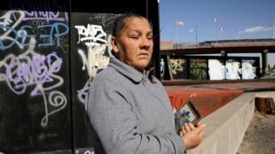 Maria Guadalupe, le 25 février 2020, tenant un portrait de son fils Sergio Hernandez près de la barrière frontalière entre le Mexique et les États-Unis, où ce dernier a été abattu, il y a presque 10 ans.