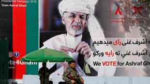 Un membre des forces de sécurité afghanes devant une affiche du candidat à la présidence afghane Ashraf Ghani à Kaboul, le 2 septembre 2019.
