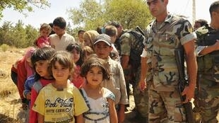 The Lebanese army helps Syrian refugees evacuated from Arsal. 4 August 2014.