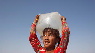 A five-year-old girl, who has been displaced by flooding, balances a water container on her head in Kakar, Pakistan