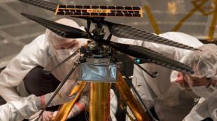 Des membres de l'équipe de la NASA inspectent l'hélicoptère, à l'intérieur du simulateur spatial, une chambre à vide de 7,62 mètres de large au laboratoire de propulsion par réaction de la NASA à Pasadena. Californie, le 1er février 2019.