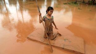 Một bé gái dùng tấm nệm làm phao chống chọi với nước lũ sau khi đập thủy điện Xe-Pian Xe-Namnoy ở tỉnh Attapeu bị vỡ. Ảnh chụp ngày 26/07/2018.