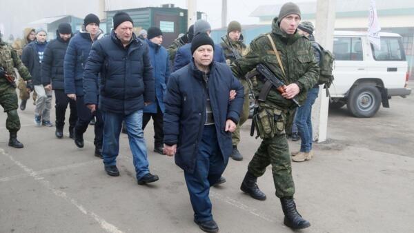 Militares escoltan a los prisioneros para iniciar el canje entre Ucrania y los separatistas.
