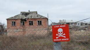 Un panneau met en garde sur la présence de mines, dans la région de Louhansk, près de la frontière avec la Russie.