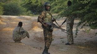 A Ugandan soldier serving with the AMISOM stands near troops from the Somali National Army in Mogadishu