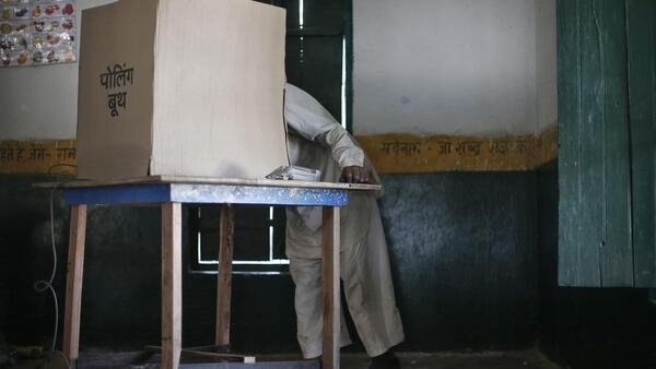 A man leans inside the booth to cast his vote at a polling station in Amka village on the outskirts of New Delhi