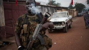 "An armed militiaman, stands guard at the entrance of the headquarters of the Muslim ""self-defence force"" group of the PK5 majority Muslim district of Bangui, 15 November 2017."