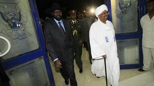 Sudan's President Omar Hassan el-Bashir (R) is welcomed by First Vice President Salva Kiir Mayardit (L) after arriving from Chad
