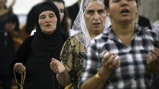 Christians pray in the Church of Mar Afram in Qaraqush after fleeing Mosul on July 19