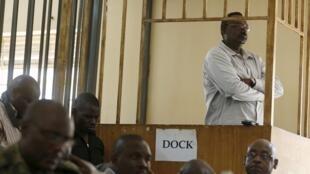 Le général David Sejusa debout dans le box des accusés devant la cour martiale, à Makindye, près de Kampala, le 2 février 2016.