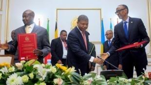 Le président angolais Joao Lourenço (au centre) sert la main du président rwandais Paul Kagame après la signature d'un accord avec le président ougandais Yoweri Museveni (à gauche), le 21 août 2019.