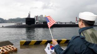 ទាហានកូរ៉េខាងត្បូង លើកទង់ជាតិស្វាគមន៍នាវាមុជទឹកបាតសមុទ្ររបស់អាមេរិក USS-Michigan ដែលទៅដល់កំពង់ផែBusan ថ្ងៃ២៥ មេសា២០១៧