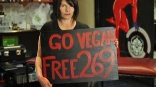 Mulher segura cartaz da associação 269Life