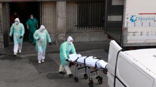 图为西班牙马德里一家医院抬出新冠病毒疫情死亡者 2020年3月25日 照片