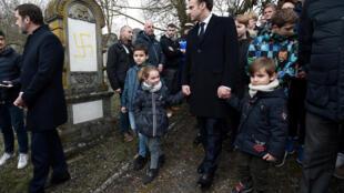 O presidente francês Emmanuel Macron visita túmulos vandalizados com suásticas nazistas no cemitério judaico da Alsácia, em Quatzenheim, na França, em 19 de fevereiro de 2019.