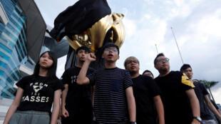"""Hoàng Chi Phong (giữa) và các bạn hô khẩu hiệu sau khi trùm vải đen lên """"Hoa lan vàng"""", biểu tượng việc trao trả Hồng Kông để đòi dân chủ, 26/06/2017."""