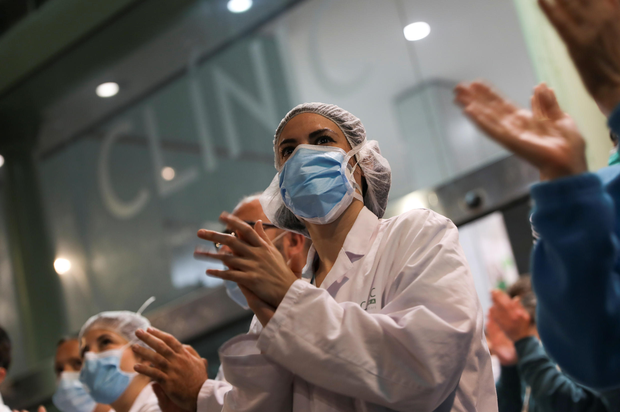 Health workers from Clinic hospital applaud citizens who show them gratitude from their balconies and windows, during the coronavirus disease (COVID-19) outbreak, in Barcelona, Spain, March 26, 2020