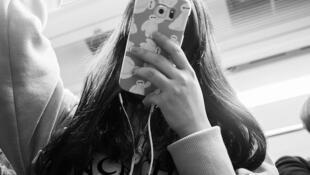Une adolescente utilisant son mobile dans les transports en commun.