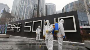 北京三里屯正在消毒的工作人員 攝於2020年2月13日 Workers in protective suits disinfect a commercial complex with sanitizing equipment, following an outbreak of the novel coronavirus in the country, in Beijing's Sanlitun, China February 13, 2020.