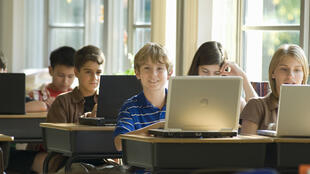 Des écoliers travaillant avec des ordinateurs portables (image d'illustration).
