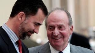 O rei Juan Carlos (d) conversa com seu filho, o princípe Felipe, que assumirá o trono da Espanha