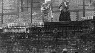 Le 26 août 1961, des hommes discutent avec leurs amies derrière une clôture à la gare Stettiner Bahnhof à Berlin.