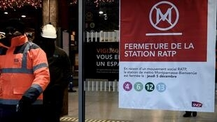 "Workers stand next to a sign reading ""metro lines closed"" at Montparnasse railway station in Paris, 5 December, 2019."