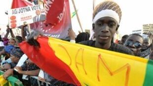 Na sexta-feira, um eleitor carrega bandeira no último comício de Macky Sall, antes das eleições presidências deste domingo, no Senegal..