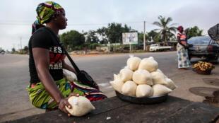 Une vendeuse d'attiéké, préparation issue du manioc, sur le bord de la route menant de San Pedro à Grand Lahou, dans le sud-ouest de la Côte d'Ivoire, en février 2014.