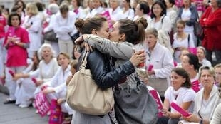 Two young women kiss in front of a demonstration against gay marriage in Marseille