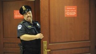 Policial segura a porta da sala onde Petraeus presta depoimento