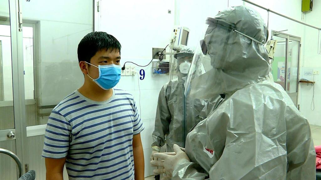 Thứ trưởng Y tế Việt Nam Nguyễn Trường Sơn (P) nói chuyện với một người tại khu vực cách ly của một bệnh viện ở Thành phố Hồ Chí Minh, nơi có hai người Trung Quốc nhiễm virus corona. Ảnh chụp ngày 23/01/2020.