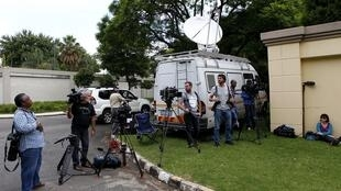 Journalists wait outside Nelson Mandela's house before announcements that he had been discharged from an undisclosed hospital