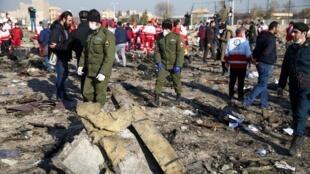 Des agents de sécurité et des employés du Croissant-Rouge sur le site où l'avion d'Ukraine International Airlines s'est écrasé, dans la banlieue de Téhéran, le 8 janvier 2020.