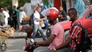 Deux jeunes masqués circulent à Port-au-Prince en Haïti, le 20 mars 2020.