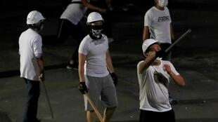 Men in white T-shirts with poles are seen in Yuen Long after they attacked anti-government demonstrators at a train station in Hong Kong, 22 July 2019.