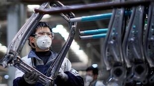 Employé portant un masque de protection en raison du coronavirus sur une ligne de production de l'équipementier Yanfeng, à Shanghai, le 24 février 2020.