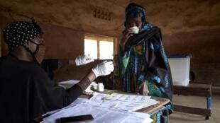Mwanamke huyu akitumia barakoa kwa kujikinga na maambukizi ya Corona anaajiandaa kupiga kura huko Bamako Machi 29, 2020.