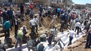 Enterro coletivo dos mortos do massacre de Houla, na Síria.