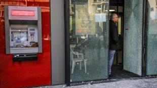 Un Libanais se tient à l'entrée d'une banque à Tripoli, le 22 janvier 2020.