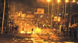 Youths gather on the street near burning fires in the Chaudron neighbourhood in Saint-Denis, Réunion
