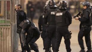 Policiais de elite revistam homens nas cercanias do apartamento ocupado por terroristas no centro de Saint-Denis