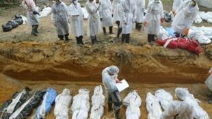 Des responsables thaïlandais enterrent en masse les victimes du tsunami à Takuapa, à près de 130 km au nord de l'île thaïlandaise de Phuket, dans cette photo datée du 1er janvier 2005.