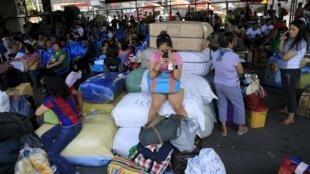 Passageiros esperam um ônibus no terminal de Manila neste sábado, enquanto as autoridades organizavam a retirada de milhares de pessoas de áreas de risco.