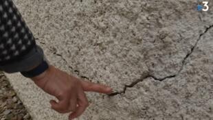 Un habitante muestras una grieta en la pared exterior de su casa.
