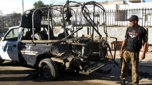 A policeman stands next to a police vehicle damaged by a suicide bomb blast in Pakistan's northwestern city of Bannu.