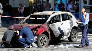 Les enquêteurs ukrainiens inspectent l'épave de la voiture que conduisait le journaliste Pavel Cheremet lorsqu'elle a explosé, dans le centre ville de Kiev, mercredi 20 juillet 2016.