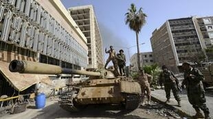 Libyan armed men climb on top of a tank outside the Central Bank, near Benghazi port,