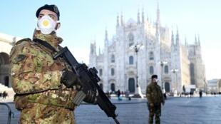 Oficiais militares usando máscaras ao lado de fora da catedral de Duomo que foi fechada por causa do surto de coronavírus. Milão, Itália, 24/02/ 2020.